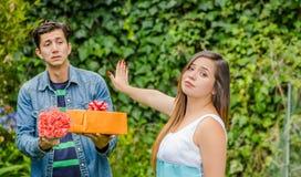 Ciérrese para arriba del hombre borroso que sostiene un regalo y las flores con la cara chocada después del ven a su novia el est imagen de archivo