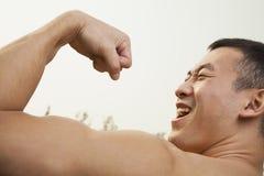Ciérrese para arriba del hombre confiado, muscular, joven que muestra apagado y que dobla su bíceps Foto de archivo libre de regalías