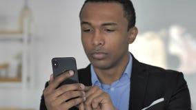 Ciérrese para arriba del hombre de negocios afroamericano casual Using Smartphone para el comercio en línea almacen de metraje de vídeo