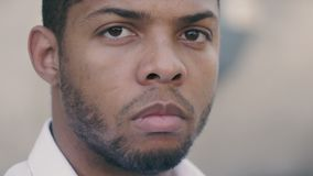 Ciérrese para arriba del hombre de negocios afroamericano serio que mira atento en la cámara al aire libre almacen de video