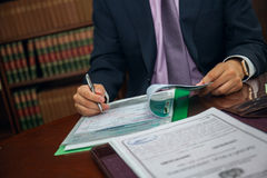 Ciérrese para arriba del hombre de negocios del abogado que se sienta en la tabla y el documento de firma Imagen de archivo