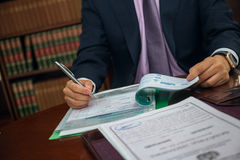 Ciérrese para arriba del hombre de negocios del abogado que se sienta en la tabla y el documento de firma Imágenes de archivo libres de regalías