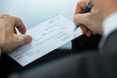 Ciérrese para arriba del hombre de negocios Filling Blank Cheque en el escritorio imagen de archivo libre de regalías
