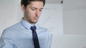 Ciérrese para arriba del hombre de negocios joven Working en el ordenador portátil metrajes