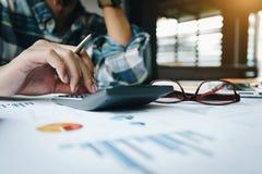 Ciérrese para arriba del hombre de negocios o del contable que trabaja en la calculadora para calcular datos de negocio, y del do foto de archivo