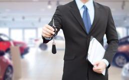 Ciérrese para arriba del hombre de negocios o del vendedor que da llave del coche foto de archivo libre de regalías