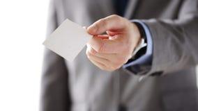 Ciérrese para arriba del hombre de negocios que da la tarjeta en blanco blanca almacen de video