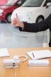 Ciérrese para arriba del hombre de negocios que da los pulgares para arriba en su escritorio Imágenes de archivo libres de regalías