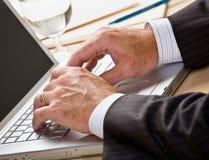 Ciérrese para arriba del hombre de negocios que pulsa en la computadora portátil Fotos de archivo libres de regalías