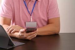 ciérrese para arriba del hombre de negocios que trabaja con el teléfono móvil en el escritorio de madera en oficina moderna con e Fotografía de archivo