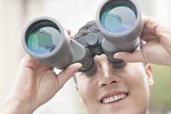 Ciérrese para arriba del hombre de negocios sonriente que mira a través de los prismáticos, reflexión azul en el vidrio Foto de archivo libre de regalías