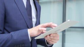 Ciérrese para arriba del hombre de negocios Working en la tableta y el caminar a la oficina, al aire libre metrajes