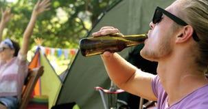Ciérrese para arriba del hombre del inconformista que bebe una cerveza almacen de metraje de vídeo