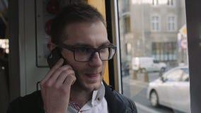 Ciérrese para arriba del hombre joven hermoso que habla por el teléfono en tranvía almacen de video