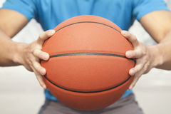 Ciérrese para arriba del hombre joven, midsection, llevando a cabo un baloncesto Imágenes de archivo libres de regalías