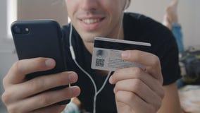 Ciérrese para arriba del hombre joven que hace compras en línea con la tarjeta y el smartphone de crédito en casa mientras que mi almacen de video