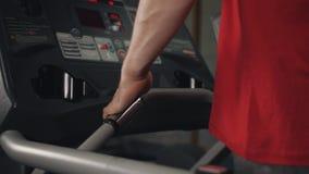 Ciérrese para arriba del hombre que activa en la rueda de ardilla en el gimnasio y que supervisa la información que él ve en la p almacen de video