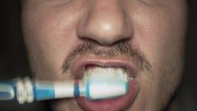 Ciérrese para arriba del hombre que cepilla sus dientes con un cepillo de dientes Hombre con las cerdas que cepillan sus dientes  almacen de metraje de vídeo