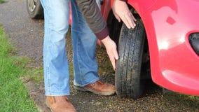 Ciérrese para arriba del hombre que comprueba la pisada del neumático o del neumático almacen de metraje de vídeo
