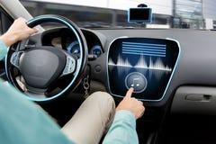 Ciérrese para arriba del hombre que conduce el coche con el sistema audio Fotografía de archivo libre de regalías