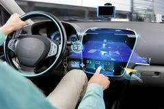 Ciérrese para arriba del hombre que conduce el coche con el sistema de navegación Foto de archivo libre de regalías