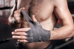 Ciérrese para arriba del hombre que envuelve la mano en cinta del boxeo Imagen de archivo libre de regalías