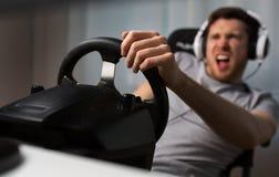 Ciérrese para arriba del hombre que juega al videojuego de las carreras de coches Imagen de archivo libre de regalías