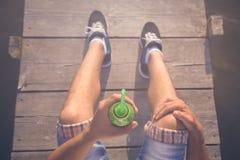 Ciérrese para arriba del hombre que sostiene el smoothie del jugo del kiwi en muelle de madera Fotografía de archivo