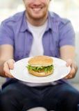 Ciérrese para arriba del hombre que sostiene la hamburguesa en la placa en casa Fotos de archivo libres de regalías