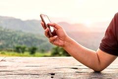 Ciérrese para arriba del hombre que usa el teléfono elegante móvil con backgro del paisaje Imagen de archivo libre de regalías