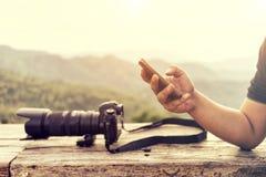 Ciérrese para arriba del hombre que usa el teléfono elegante móvil con backgro del paisaje Fotografía de archivo libre de regalías