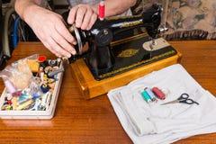 Ciérrese para arriba del hombre que usa la máquina de coser pasada de moda Imagen de archivo libre de regalías