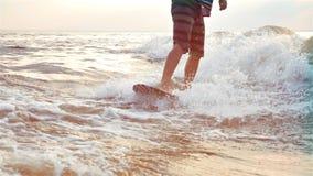 Ciérrese para arriba del hombre wakesurfing en la puesta del sol en la cámara lenta Deporte del extremo del agua metrajes