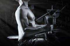 Ciérrese para arriba del individuo muscular del culturista que hace ejercicios con los pesos Imagenes de archivo