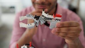 Ciérrese para arriba del ingeniero de sexo masculino que piensa sobre el detalle robótico
