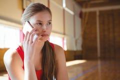 Ciérrese para arriba del jugador de básquet de sexo femenino que habla en el teléfono Imagen de archivo libre de regalías