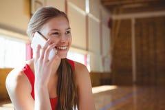 Ciérrese para arriba del jugador de básquet de sexo femenino sonriente que habla en el teléfono Imágenes de archivo libres de regalías
