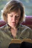 Ciérrese para arriba del libro de lectura de la mujer con la iluminación posterior Fotos de archivo libres de regalías