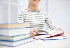 Ciérrese para arriba del libro de lectura de la mujer joven en la escuela Fotografía de archivo libre de regalías