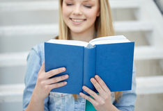 Ciérrese para arriba del libro de lectura de la mujer joven en la escuela Imagen de archivo