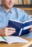 Ciérrese para arriba del libro de lectura del estudiante en la escuela Fotos de archivo