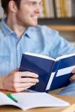 Ciérrese para arriba del libro de lectura del estudiante en la escuela Imagenes de archivo