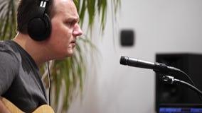 Ciérrese para arriba del músico que canta y que toca la guitarra eléctrica en el estudio casero de la música
