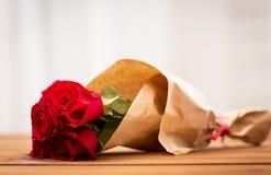 Ciérrese para arriba del manojo de las rosas rojas envuelto en el papel Imagenes de archivo