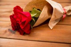 Ciérrese para arriba del manojo de las rosas rojas envuelto en el papel Imágenes de archivo libres de regalías