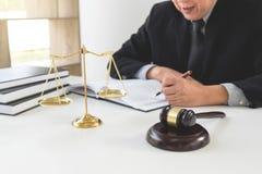 Ciérrese para arriba del mazo, del abogado de sexo masculino o del juez trabajando con los libros de ley, imagen de archivo