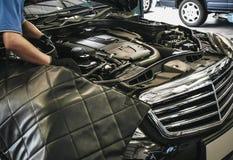 Ciérrese para arriba del mecánico de automóviles de sexo masculino que trabaja en el motor en la reparación auto fotografía de archivo