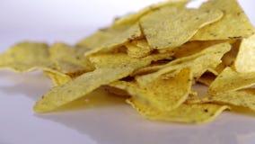Ciérrese para arriba del montón de los nachos dispersados en la tabla giratoria blanca almacen de metraje de vídeo