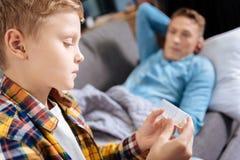 Ciérrese para arriba del muchacho pre-adolescente que detiene al organizador de la píldora imagenes de archivo