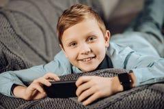 Ciérrese para arriba del muchacho pre-adolescente que juega en su teléfono Foto de archivo libre de regalías